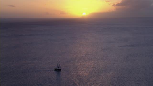 single sailboat on vast ocean at sunset. - yacht stock videos & royalty-free footage
