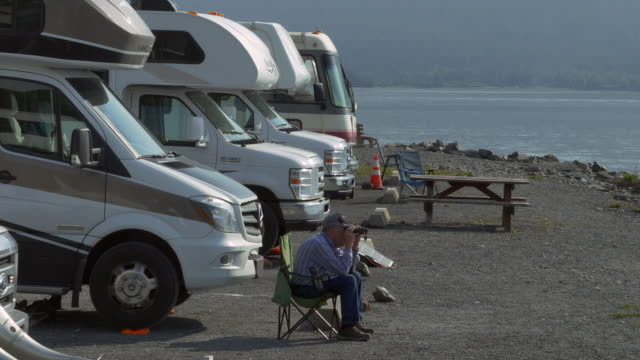 single senior man enjoying view in front of motor homes with binoculars - camper van stock videos & royalty-free footage
