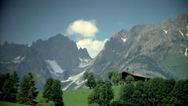 vidéos et rushes de single story chalet on top of hill w/ trees fg, austrian alps mountains bg. no people. - chalet