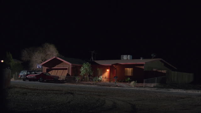 WS Single Story Modern Wooden Brown House With Attached Garage Illuminated At Night