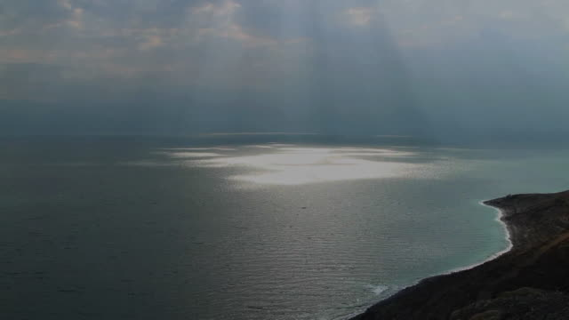 single sun rays on the dead sea from the judean desert cliffs