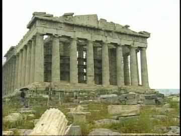 single tourist with an umbrella walks on the acropolis past the parthenon as it undergoes restoration. - fronton bildbanksvideor och videomaterial från bakom kulisserna