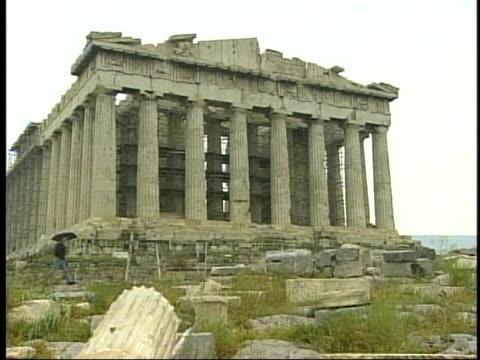 a single tourist with an umbrella walks on the acropolis past the parthenon as it undergoes restoration - ペディメント点の映像素材/bロール