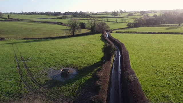 a single track country road from a drone - horizon over land stock videos & royalty-free footage