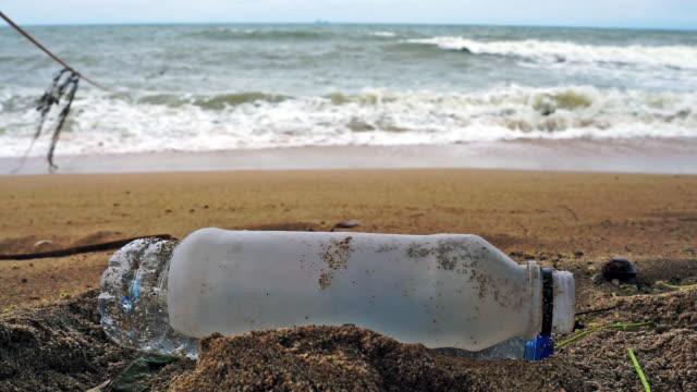 vídeos de stock e filmes b-roll de single use ocean plastic pollution washed up on the beach - utilização única