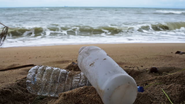 single use plastic pollution washed up on the beach - milk bottle stock videos & royalty-free footage