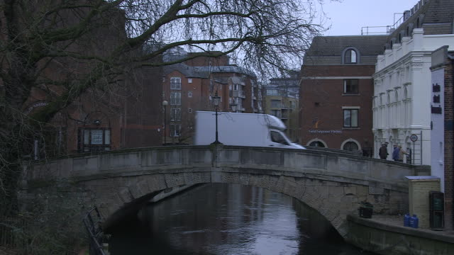 vídeos de stock e filmes b-roll de a single white van drives over high bridge on london street, crossing the river kennet, in reading at dusk, england, uk. - berkshire inglaterra