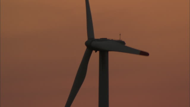 CU Single wind turbine against orange sunset sky, Huitengxile, Inner Mongolia, China