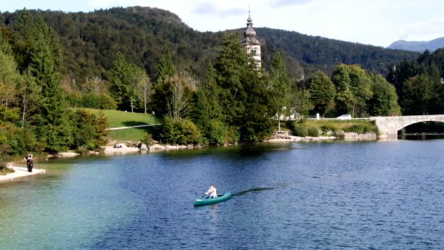 vídeos de stock e filmes b-roll de single woman canoeing on the lake - eslovénia
