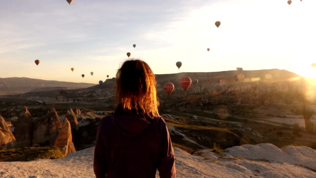 single woman is walking while watching hot air balloons in cappadocia - good posture stock videos & royalty-free footage