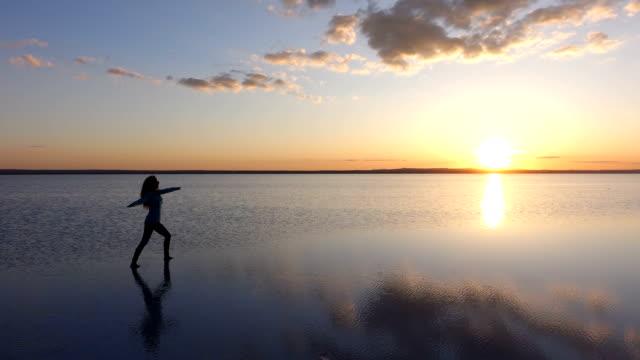 stockvideo's en b-roll-footage met alleenstaande vrouw mediteren in een kalm meer bij zonsondergang - midden oosterse etniciteit