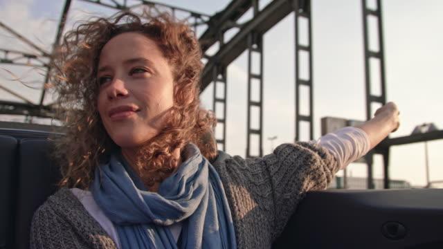 vídeos de stock, filmes e b-roll de single woman raising arms in a convertible car while driving over a bridge (hackerbrücke - münchen) - ponto de vista de carro