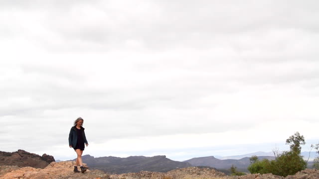 single woman traveller walking along the ridge of a mountain