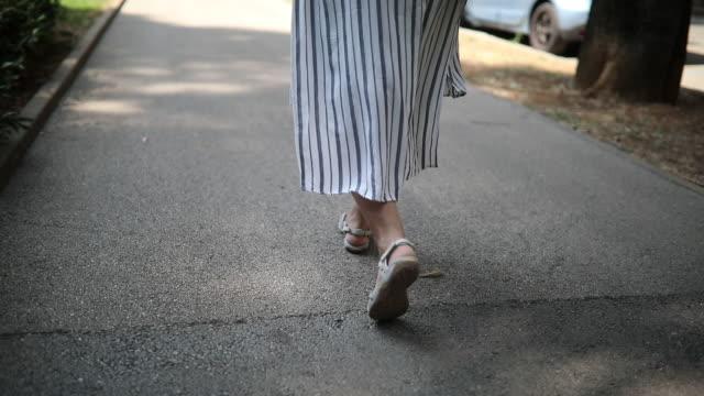 vídeos de stock e filmes b-roll de single woman walking in the park - distante