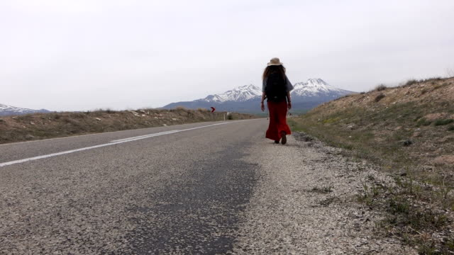single woman walking on empty road with a high attitude mountain scenery - anatolia stock videos and b-roll footage