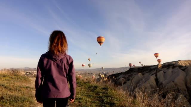 single woman walking while watching hot air balloons in Cappadocia
