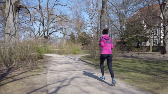 single young woman jogging during coronavirus pandemic - march month stock videos & royalty-free footage
