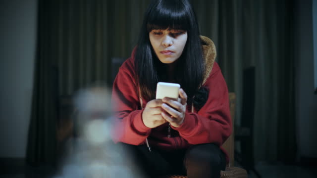 single young woman using smart phone at night. - three quarter length stock videos & royalty-free footage