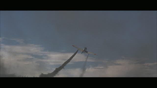vídeos de stock e filmes b-roll de ws pan single-engine plane in flight and steaming smoke - formato letterbox