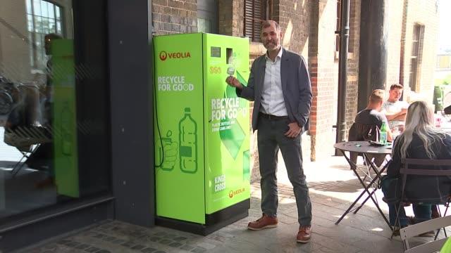 single-use plastics to be banned from april 2020; england: london: ext hand putting plastic bottle into recycling bank reporter to camera sot cutaway... - slit och släng bildbanksvideor och videomaterial från bakom kulisserna