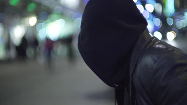 sinister bearded man in hood looking around in busy shopping street at night - criminal stock videos and b-roll footage