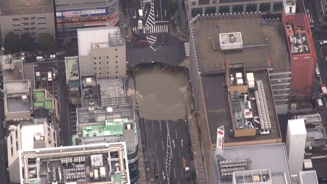 vídeos de stock, filmes e b-roll de a sinkhole 20 meters long and 15 meters wide occurred in front of jr hakata station here on november 8 fukuoka japan but no injuries were reported... - prefeitura de fukuoka