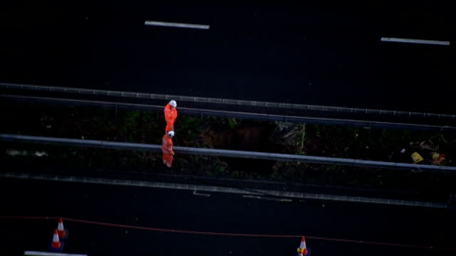 kent m2 motorway views aerials of sink hole in central reservation of m2 motorway and emergency service workers beside - イングランド ケント点の映像素材/bロール