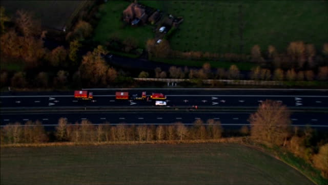 stockvideo's en b-roll-footage met sinkhole appears in m2 motorway; england: kent: m2 motorway: ext air views - aerials of sink hole in central reservation of m2 motorway and emergency... - verschijning