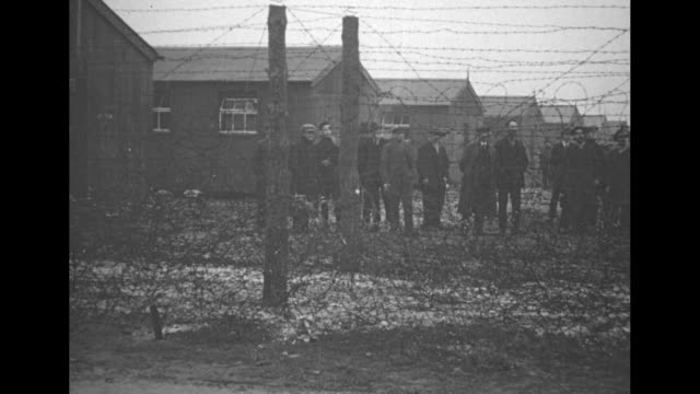 stockvideo's en b-roll-footage met sinn fein men stand behind a barbed wire fence with barracks behind them they march two by two stand in a line and numerous men walk past with towels... - 1921