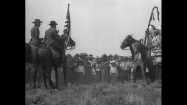 stockvideo's en b-roll-footage met ms sioux and cheyenne men in traditional garb ride horses toward camera / ls 7th cavalry rides toward camera / ms front of line of cavalry one... - amerikaans indiaanse etniciteit