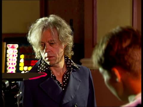 sir bob geldof interviewed on set of short film in which he plays himself england london hammersmith int camera crew on film set actors in costume... - bob geldof stock videos & royalty-free footage