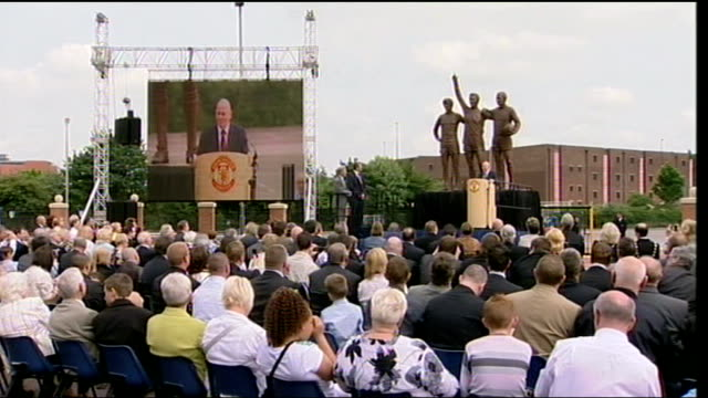 sir bobby charlton denis law and george best statue unveiled at old trafford ferguson and audience listening to speaker sot / general view of united... - 全体撮影点の映像素材/bロール