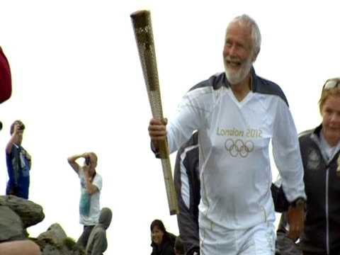 sir chris bonington reaches mount snowdon's summit with the olympic torch - flaming torch stock videos & royalty-free footage
