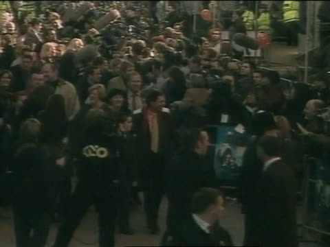 sir cliff richard & nephew walking down crowded walkway at leicester square, fans & press behind barricades, entering odeon theatre. - cliff richard stock videos & royalty-free footage