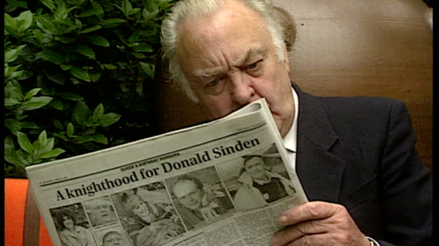 sir donald sinden dies aged 90 t14069701 london ext various of sir donald sinden reading newspaper with article on reverse about his knighthood - article stock videos & royalty-free footage