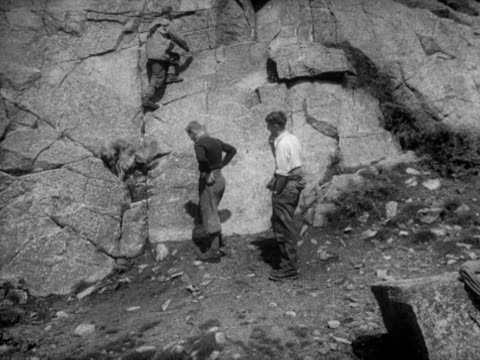vídeos de stock e filmes b-roll de sir edmund hillary sir john hunt and eric shipton start to climb a rockface in the lake district - paredão rochoso