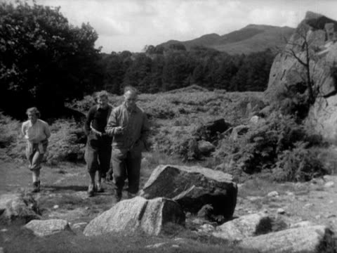 stockvideo's en b-roll-footage met sir edmund hillary sir john hunt eric shipton and lady hunt walk up to a rockface during their walk in the lake district countryside - rotsmuur