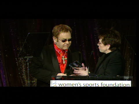 sir elton john receives a plaque from billie jean king at the women's sports foundation presents inaugural the billies at the beverly hilton in... - ビリー・ジーン・キング点の映像素材/bロール