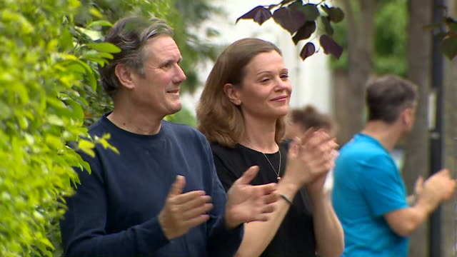 sir keir starmer mp labour leader and his wife on their doorstep clapping for carers during the coronavirus pandemic - steps and staircases stock videos & royalty-free footage