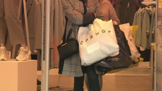 sir philip green's arcadia 'near collapse'; wales: ext shoppers wearing face masks leaving store with 'topshop' bags - leaf stock videos & royalty-free footage