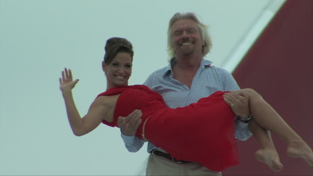 sir richard branson lifts singer sarah harding in his arms as they walk on aircraft wing at miami airport after virgin atlantic flight to celebrate... - picking up stock videos & royalty-free footage