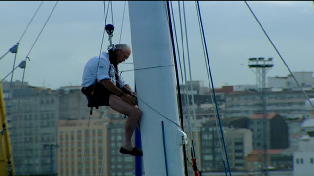 stockvideo's en b-roll-footage met sir robin knoxjohnston rejoins five oceans race spain la coruna ext general view of yacht 'saga insurance' in harbour sir robin knoxjohnston in hoist... - hijsen