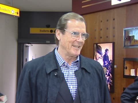 vídeos de stock, filmes e b-roll de sir roger moore poses for pictures at heathrow shortly after recovering from a heart problems the former james bond actor was en route to his home in... - james bond trabalho conhecido