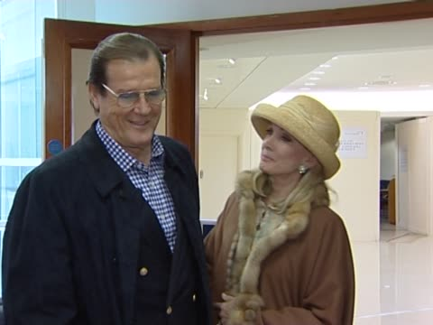 vídeos de stock, filmes e b-roll de sir roger moore poses for pictures at heathrow with his fourth wife kristina 'kiki' tholstrup shortly after recovering from a heart problems the... - james bond trabalho conhecido
