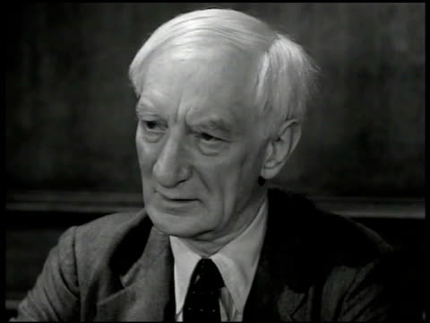 Sir William Beveridge at desk w/ men 'My plan for social security in Britain is to combine into one comprehensive scheme insure an income sufficient...