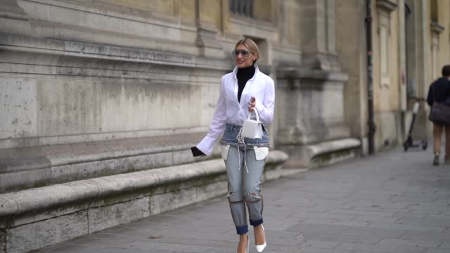 sira pevida wears sunglasses a black turtleneck a white shirt ripped blue denim jeans a white bag white shoes outside unravel project during paris... - top garment stock videos & royalty-free footage