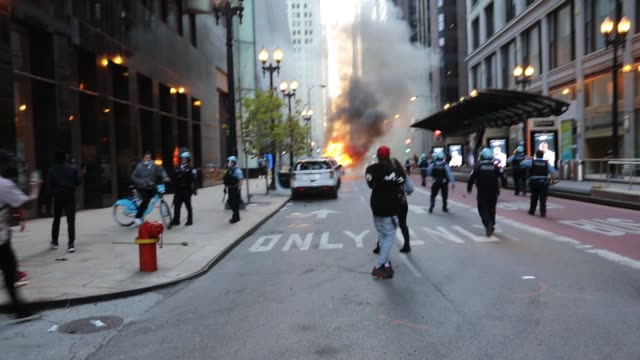 sirens are heard as a fire breaks out in the street as onlookers run watch and capture the moment on their phones while police surround the vicinity... - minnesota stock-videos und b-roll-filmmaterial