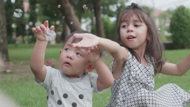 schwester und bruder haben spaß mit seifenblasen. - geschwister stock-videos und b-roll-filmmaterial