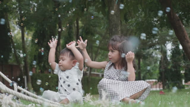 sister and brother are having fun with soap bubbles. - lawn stock videos & royalty-free footage