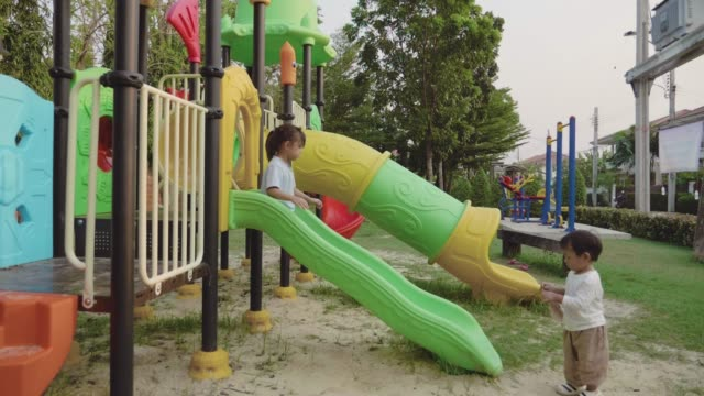 sister and brother having fun sliding on a slide in park. - parco giochi video stock e b–roll